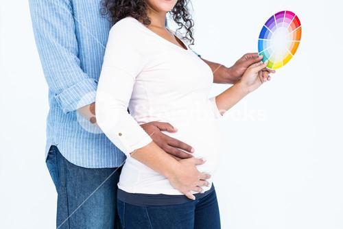 Midsection husband with wife holding color wheel