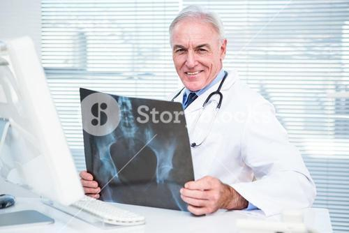 Portrait of doctor with xray sitting in front of computer