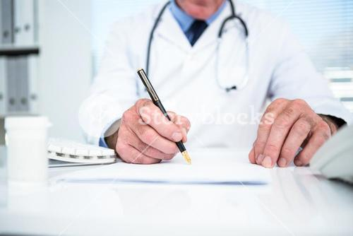 Doctor writing on paper at clinic