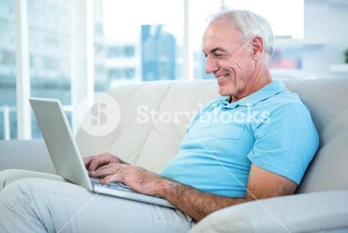 Happy senior man sitting on sofa while using laptop