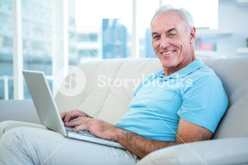 Portrait of happy senior man sitting on sofa with laptop