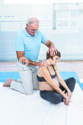 Male therapist massaging pregnant woman