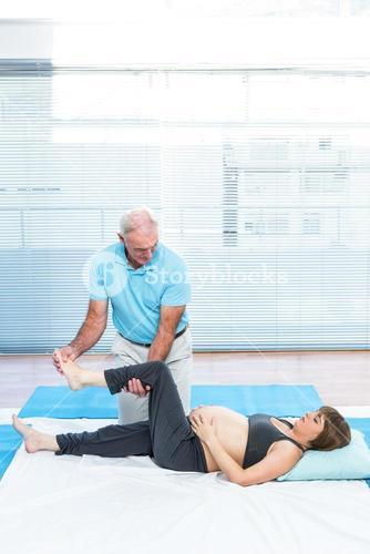 Cheerful therapist kneading to pregnant woman lying on mattress
