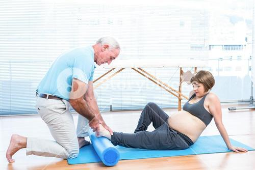 Male instructor massaging foot of pregnant woman