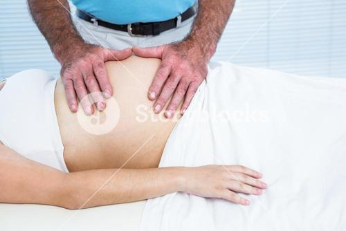 Therapist massaging belly of pregnant woman