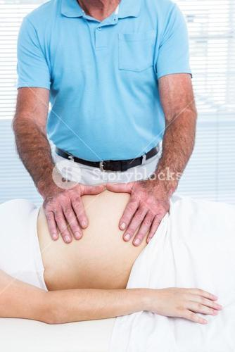 Male masseur massaging belly of pregnant woman