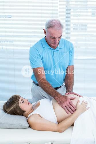 Male therapist massaging belly of pregnant woman