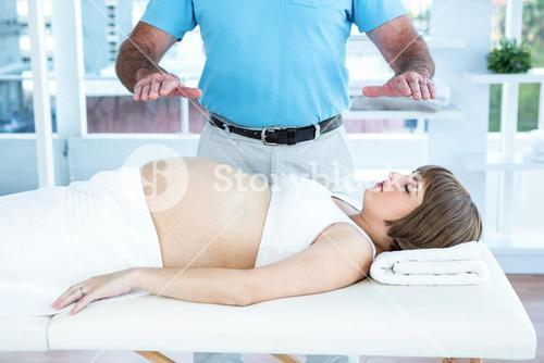 Therapist performing reiki over pregnant woman