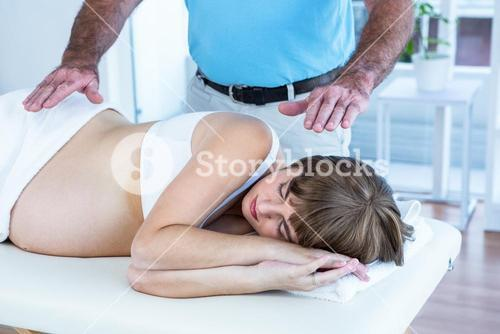 Male therapist performing reiki over pregnant woman