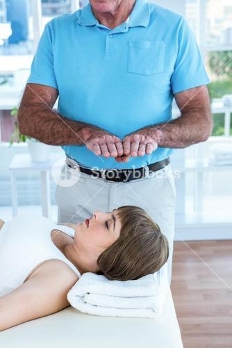 Pregnant woman relaxing while therapist performing reiki