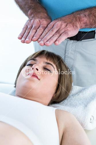 Close-up of calm woman receiving reiki treatment