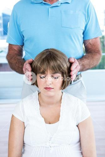 Therapist performing reiki over woman