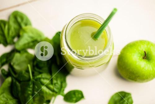Overhead view of juice with green apple and basil
