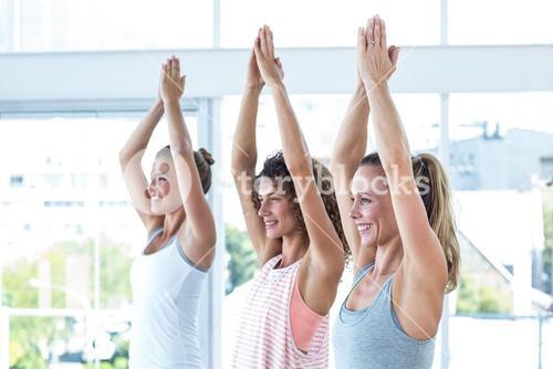 Side view of happy women with hands joined overhead