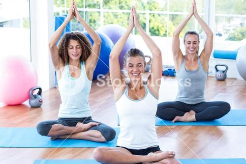 Women with hands joined overhead in lotus pose