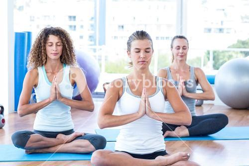 Focused women in lotus pose with hands joined