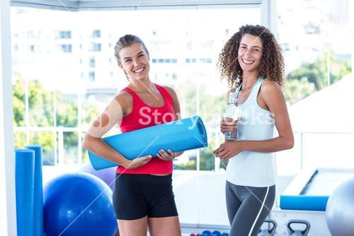 Fit women holding exercise mat and water bottle in fitness studio