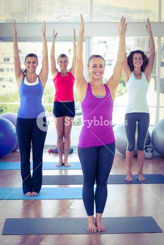 Cheerful women with arms raised in fitness studio