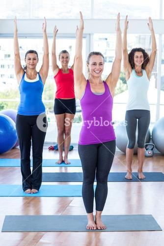Happy women in fitness studio with arms raised