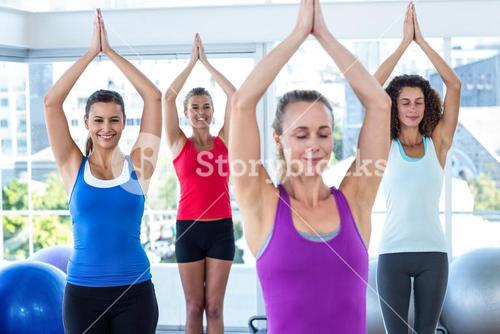 Women in fitness studio with hands joined overhead