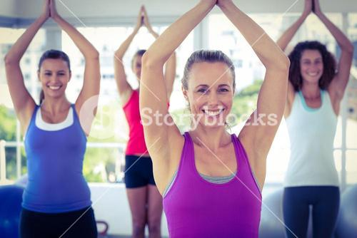 Cheerful women in fitness studio with hands joined