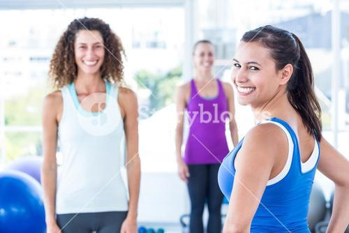 Portrait of cheerful woman with friends at fitness center