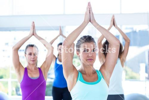 Focused women in fitness studio with hands joined