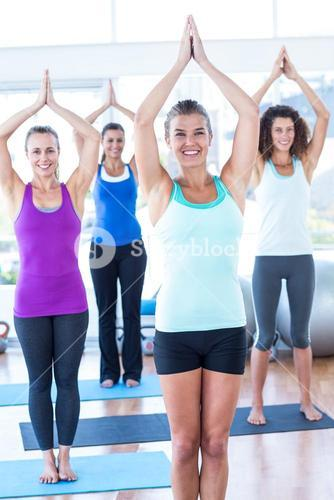 Happy and fit women with hands joined overhead in fitness studio