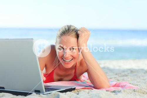 Lovely woman with her laptop at the beach