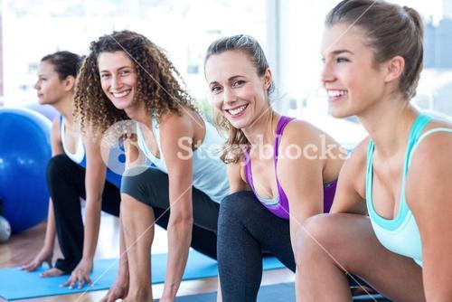Portrait of women doing high lunge pose in fitness studio