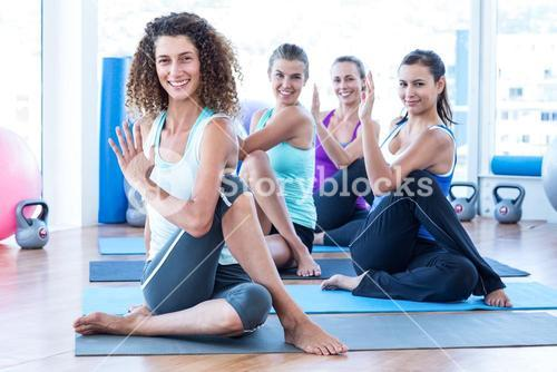 Portrait of cheerful women doing spine twisting pose