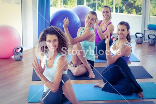 Portrait of happy women doing spine twisting pose