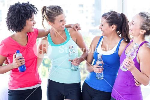 Cheerful women holding water bottle in fitness studio