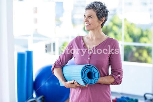 Happy thoughtful mature woman with yoga mat