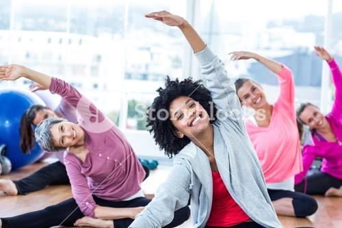 Cheerful women exercising with arms raised