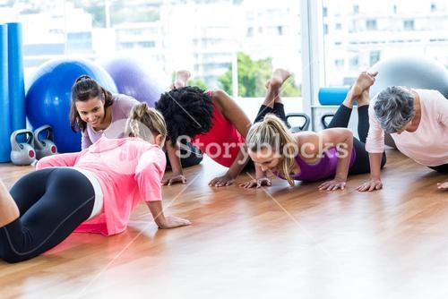 Women exercising on floor with trainer