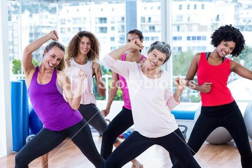 Portrait of cheerful women exercising with clasped hands