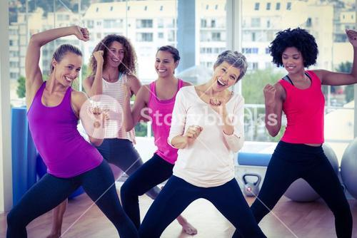 Portrait of happy women exercising with clasped hands