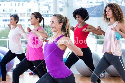 Women exercising with clasped hands and stretching