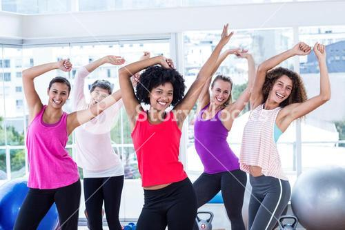 Portrait of women exercising with arms raised