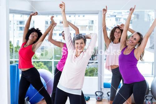 Group of cheerful women exercising with arms raised