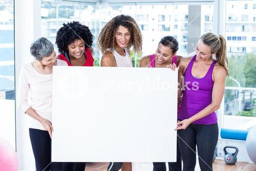 Smiling women holding board