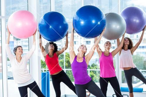 Women holding exercise balls with arms raised