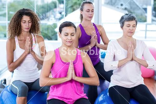 Women relaxing on exercise balls with joined hands