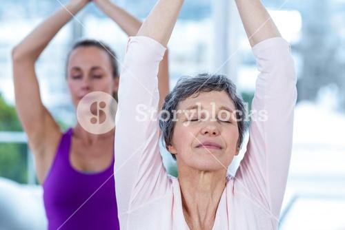 Women meditating with joined hands and eyes closed