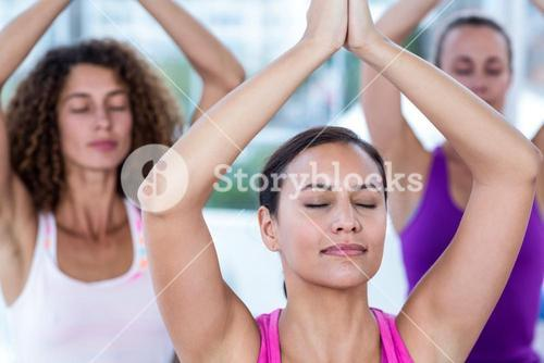 Women meditating with joined hands and arms raised