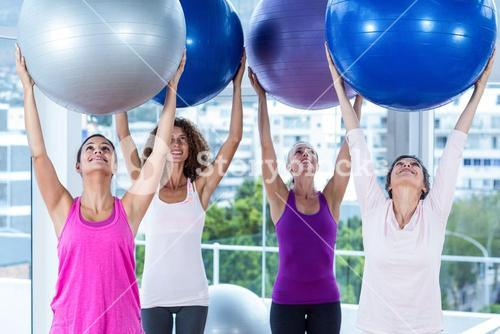 Cheerful women holding exercise balls with arms raised