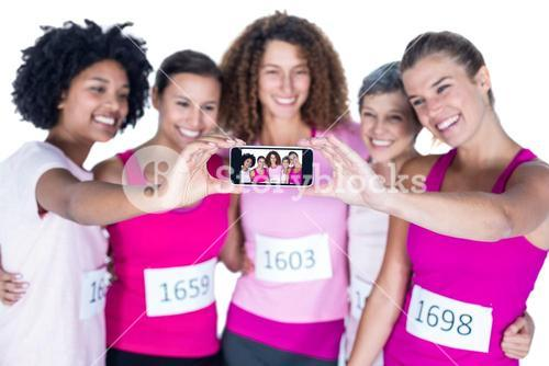 Smiling athletes taking self portrait with smartphone