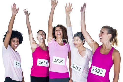 Cheerful female athletes with arms raised