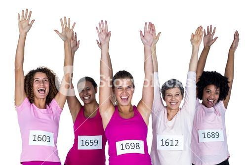 Portrait of cheerful female athletes with arms raised